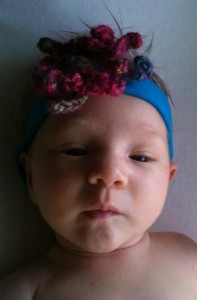 Photo of Baby DD with hand-knit flower headband on